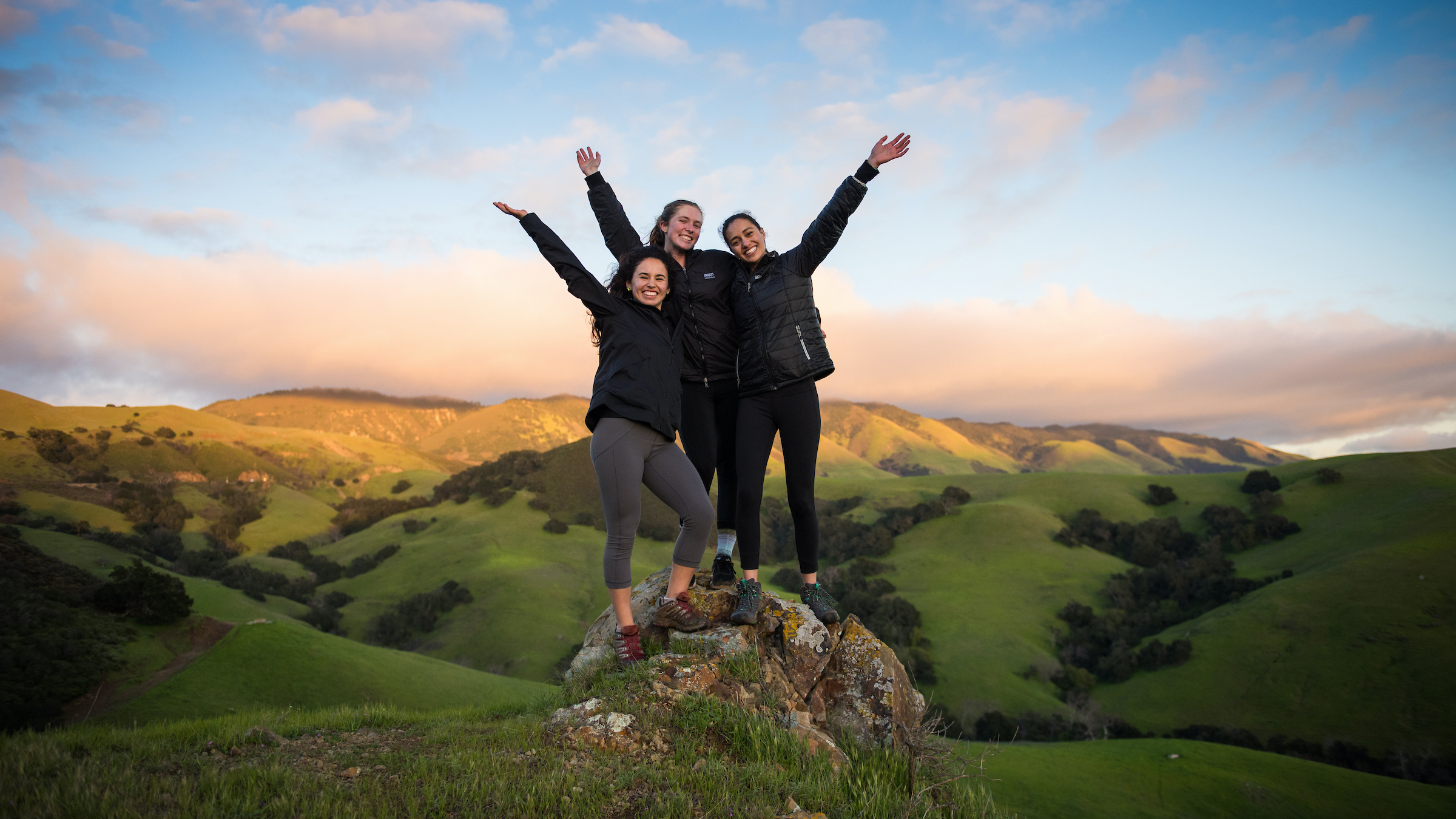 three female students reaching top of a hill