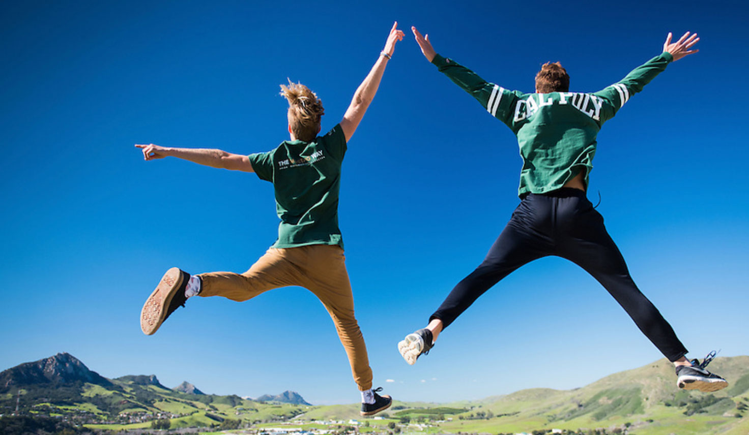 two students leap in the air and high five